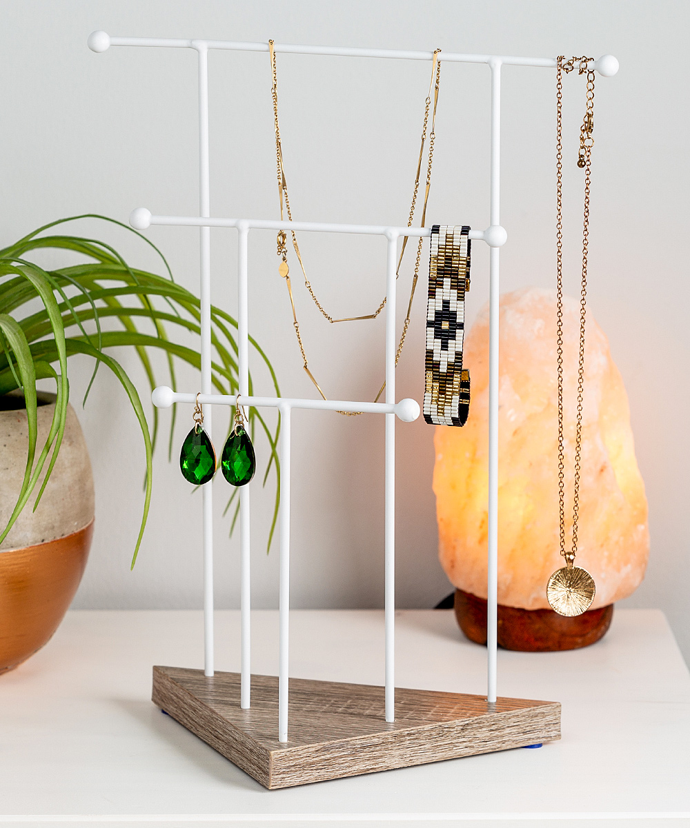 Three-Tier Triangle Jewelry Stand Three-Tier Triangle Jewelry Stand. Proudly display all of your favorite necklaces and bracelets with this tiered jewelry stand. Three different hanging levels provide ample space for future finds. 5'' W x 12.75'' H x 10'' DMDF / wireImported