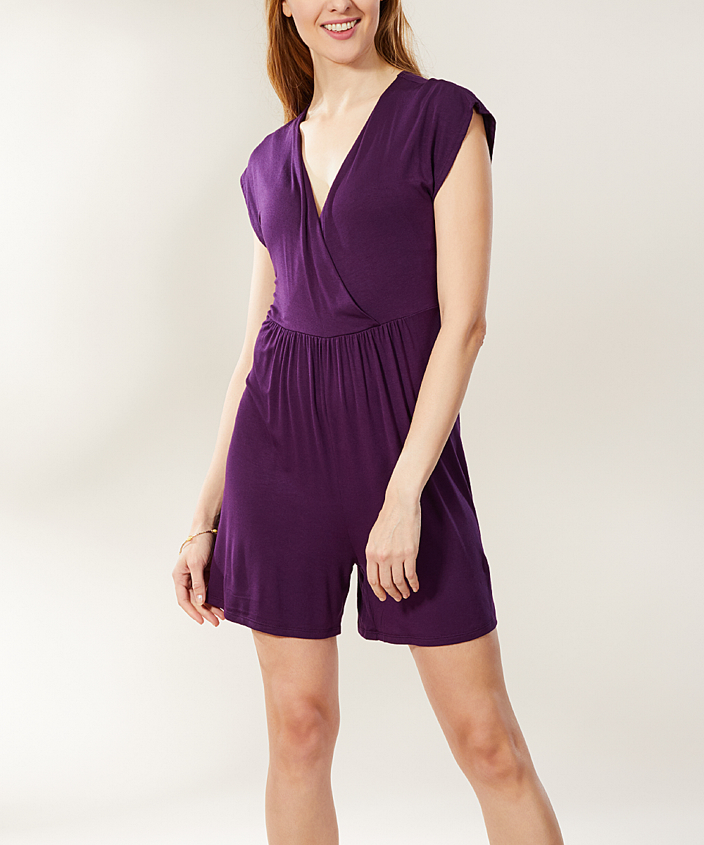 Eggplant Cap-Sleeve Surplice Romper - Women Eggplant Cap-Sleeve Surplice Romper - Women.  A gathered waist and face-framing surplice neckline enliven the solid-color style of this playful romper. Accessorize with sandals and your favorite fashion jewelry for a dynamite warm-weather look.Size S: 35'' long from high point of shoulder to hemSize S: 5'' inseam95% rayon / 5% spandexMachine wash; tumble dryAssembled in the USA using imported materialsShipping note: This item is made to order. Allow extra time for your special find to ship.